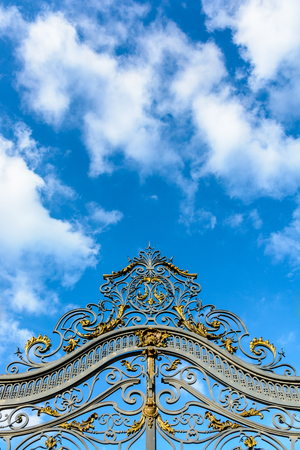 Low angle view of the richly decorated main entrance gate of the Noisiel public park, in the eastern suburbs of Paris, with golden wrought iron leaves against a deep blue sky.