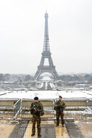 Paris, France - February 7, 2018: As part of the Vigipirate plan, two french soldiers patrol with their assault rifle in hand on the Trocadero esplanade, opposite the Eiffel tower, by a snowy day.