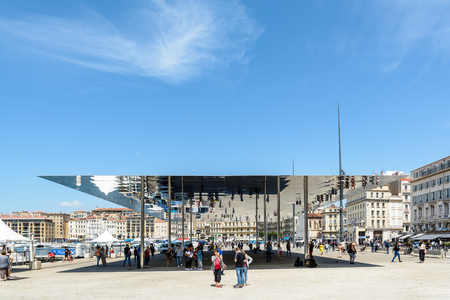 Marseille, France - May 23, 2018: People walking or standing under the sunshade by Norman Foster, a large reflective steel blade supported by slender pillars, installed in 2013 on the Old Port.