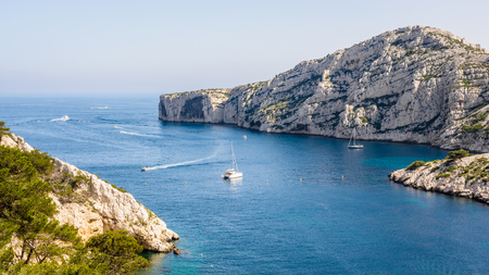 Panoramic view of the cap Morgiou on the mediterranean shore near Marseille, France, with motorboats cruising and sailboats mooring in the blue waters of the calanque de Morgiou on a sunny day. Фото со стока - 115774175