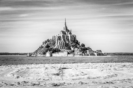 The Mont Saint-Michel tidal island in Normandy, France, seen from the polders with hay windrows drying in a field in the foreground under a bright sunlight. 스톡 콘텐츠