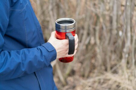 Young girl in the classic blue jacket with braided beautiful hair. Caucasian woman holds a red travel mug with hot drink in the park. Thermal cup with coffe or tea. Camping hiking lifestyle.