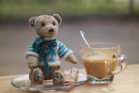 Teddy Bear toy and cup of latte on wood