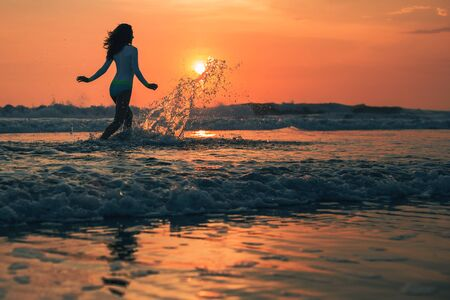 Silhouette of the woman running in the water during sunset. Stock Photo