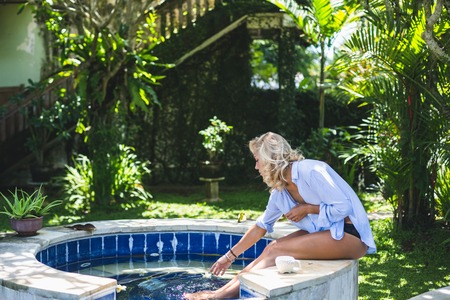 Beautiful young blonde woman in a white blue shirt in the green garden among palm trees and flowers. Girl in the jungle.