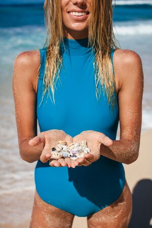 Young attractive woman in swimwear standing on coastline with deep blue water and holding seashells in hands during daytime