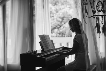 Beautiful woman playing piano. Black and white Stock Photo