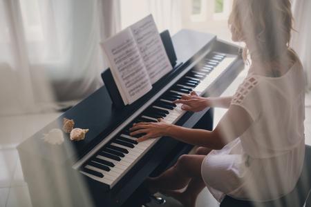 white sheet: Beautiful woman playing piano