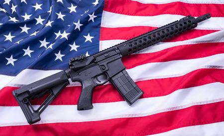 Wykonany na zamówienie karabinek AR-15 na powierzchni flagi amerykańskiej, tło. Strzał studio. Zdjęcie Seryjne