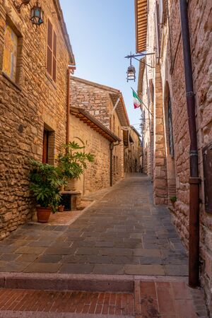 Street of the small town of Assisi, Italy, with buildings and plants on the sides 写真素材