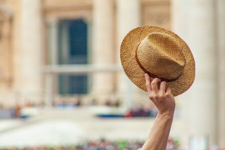 A hand holds a straw hat in greeting in St. Peter's Square, Rome, Italy Banco de Imagens