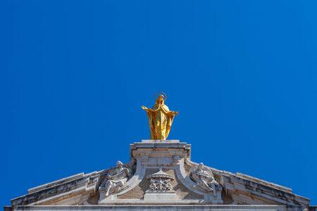 The golden Madonna on the tops of the facade of the basilica of Santa Maria degli Angeli, Assisi, Italy
