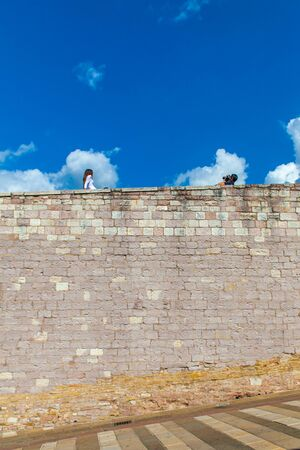 A boy punctuates a girl on the top of the wall in front of the Basilica of San Francesco in Assisi, Umbria, Italy