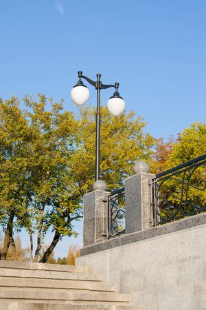 lamppost near the stairs and fence against the sky photo