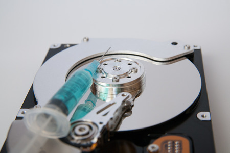 hdd: Closeup view of hdd cylinder and a syringe Stock Photo
