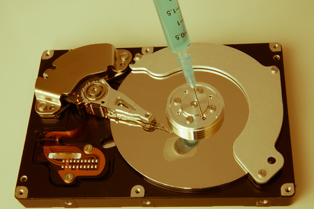 terabyte: closeup view of hdd cylinder and a syringe Stock Photo