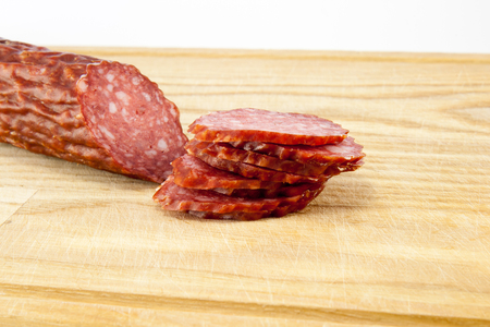 Slice of salami sausages on wooden board isolated photo