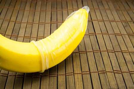 Banana with condom on wooden background