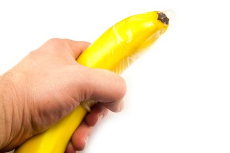 Condom on banana in hand isolated