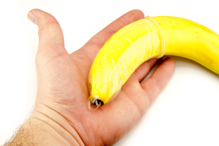 Condom on banana in hand isolated