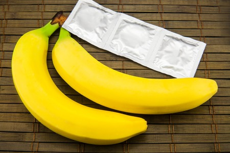 Banana with condom on wooden background. Stock image. Banco de Imagens