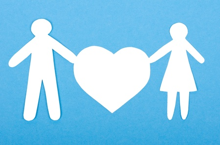 Closeup of paper people with a big heart on white background photo