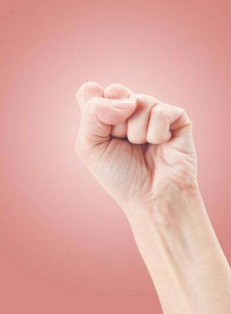 Fist. Gesture of the hand on pink background. photo