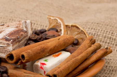 Sweets, cinnamon, nuts and coffee beans on a saucer, on burlap background Stock Photo - 12707008