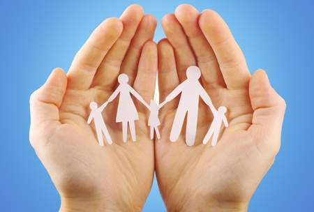 Paper family in hands isolated on blue background photo