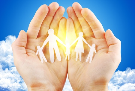hand of god: paper family in hand sun and blue sky with copyspace showing freedom or solar power concept Stock Photo