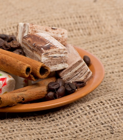 stimulant: Sweets, cinnamon, nuts and coffee beans on a saucer, on burlap background. Stock Photo