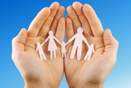 Paper family in hands isolated on blue sky