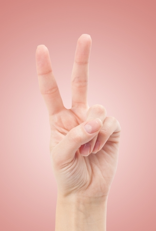 Hand with two fingers up in the peace or victory symbol. Also the sign for the letter V in sign language. photo