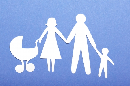 Closeup of paper family on green background photo