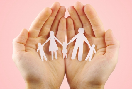 Paper family in hands isolated on pink background photo