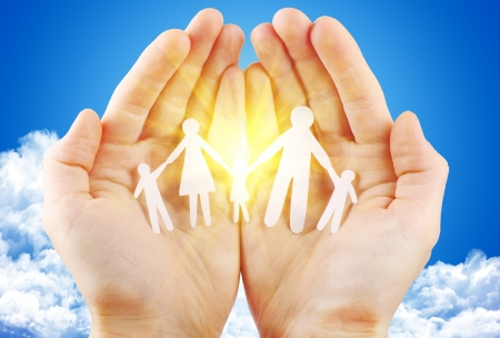 renewabel: paper family in hand sun and blue sky with copyspace showing freedom or solar power concept Stock Photo
