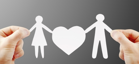 human relationship: paper family with heart in hands Stock Photo