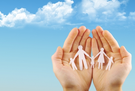 Paper family in hands isolated on blue sky  photo