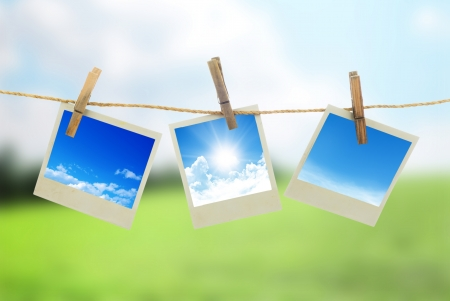 Three instant photos with sky inside hanging on the clothesline photo