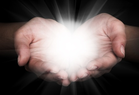 Female hands holding a brilliant star in the dark Stock Photo