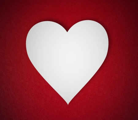 White paper heart on red background photo