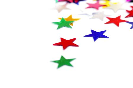 Christmas decoration of colored confetti stars against white background photo