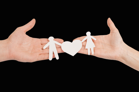 linked hands: Cutout paper chain family with the protection of cupped hands, concept for security and care Stock Photo