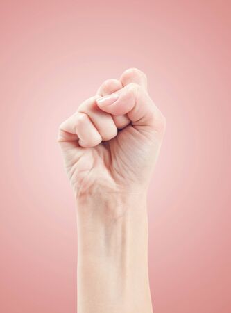 oneness: Fist. Gesture of the hand on pink background.