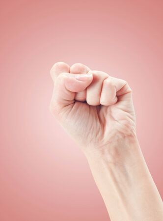 oneness: Fist Gesture of the hand on pink background. Stock Photo