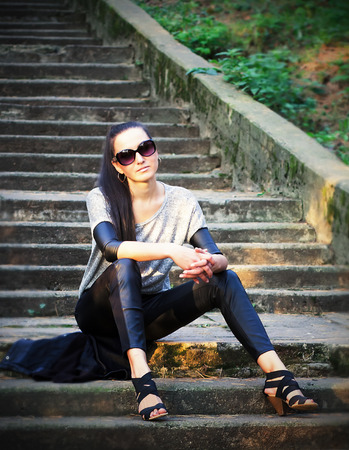 young girl in sunglasses sitting on stairs