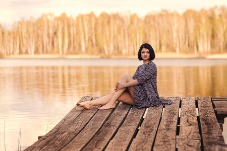 young cute girl sits on a pier in a summer dress Imagens