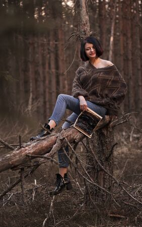 young woman with a burned book in nature