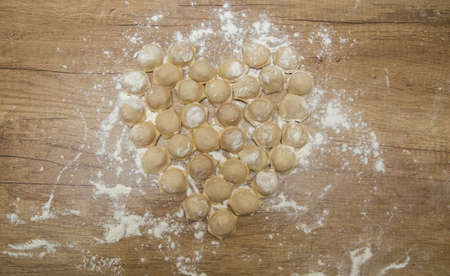 Dumplings cooked at home. Raw blinded dumplings on the table. A dish for Valentine's Day. DIY. Step by step. Step 6