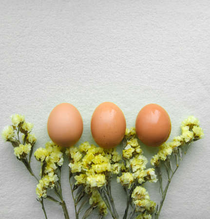 Easter egg and yellow flowers on a gray background. Color trend 2021. Vertically